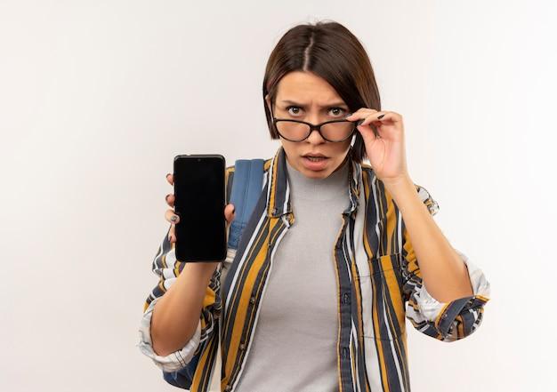 Ragazza giovane studente confusa con gli occhiali e borsa posteriore che mostra i vetri della tenuta del telefono cellulare isolati su bianco con lo spazio della copia