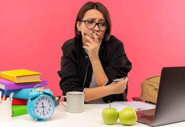 Ragazza giovane studente confuso con gli occhiali seduto alla scrivania guardando al lato mettendo la mano sul mento e sulle labbra e un altro sul braccio con la penna in esso facendo i compiti isolati sul rosa