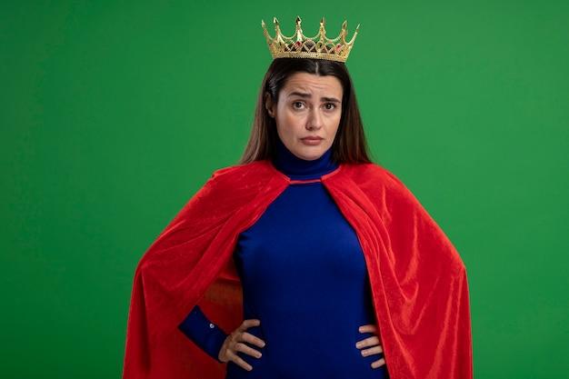 緑に分離された腰に手を置く王冠を身に着けている混乱した若いスーパーヒーローの女の子