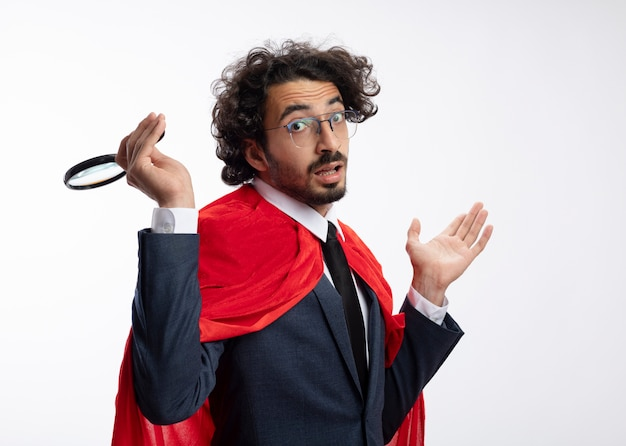 Confused young superhero man in optical glasses wearing suit with red cloak holds magnifying glass and keeps hand open isolated on white wall