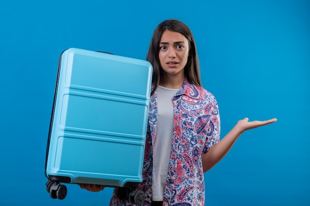 Confused young traveler woman holding travel suitcase doubtful shrugging shoulders standing on isolated blue