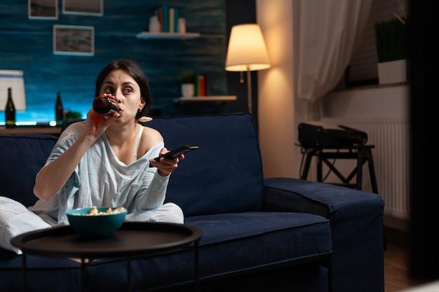 Смущенная молодая женщина пьет пиво во время просмотра фильма по телевизору