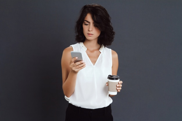 Confused young woman holding her phone and coffee in hands