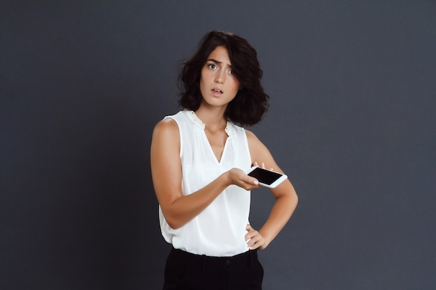 Confused young woman holding her phone in hands