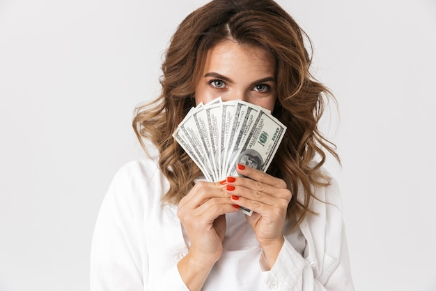 Confused young woman holding money banknotes isolated