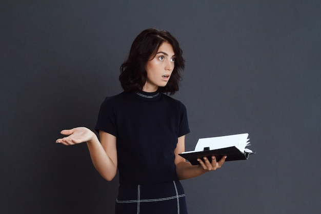 Confused young woman holding notebook in hands