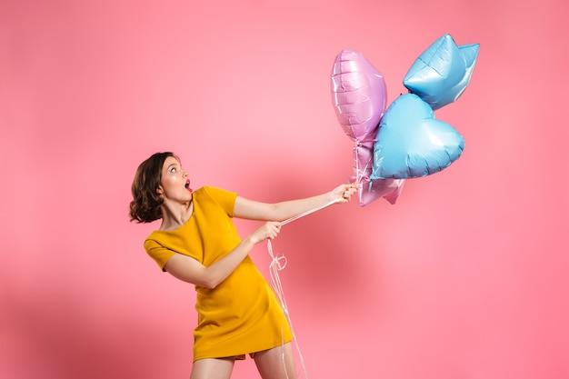風船を持って黄色のドレスで混乱している若い女性