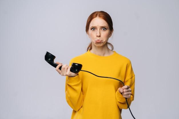 노란색 스웨터를 입은 혼란스러운 젊은 여성이 복고풍 전화기의 수화기를 들고 카메라를 쳐다보고 있다