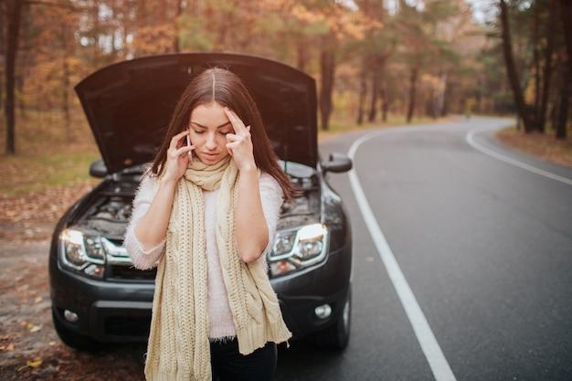 路上で壊れた車のエンジン車の修理を見て混乱している若い女性