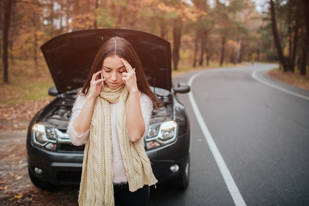 Confused young woman looking at broken down car engine car repair on the street