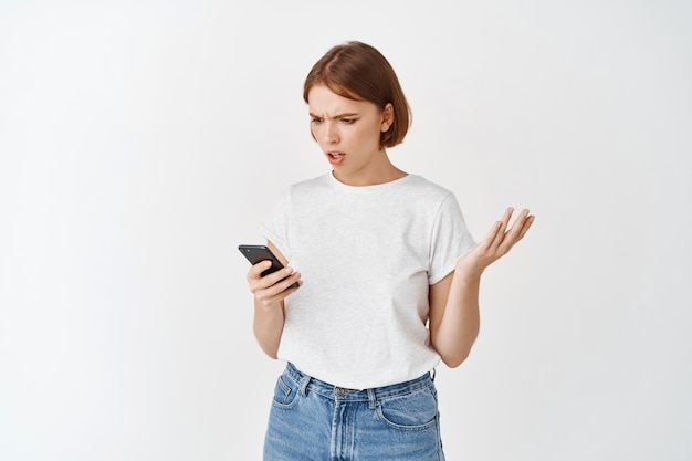 Confused young woman looking at mobile phone with questioned expression, shrugging troubled, standing against white wall