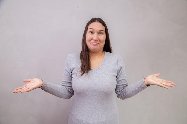 텍스트에 대 한 공간을 가진 회색 배경에 혼란 스 러 워 젊은 여자. 여자는 그녀가 회색 배경 위에 고립 된 것을 모른다고 말하는 그녀의 손을 잡고. 개념이 없다