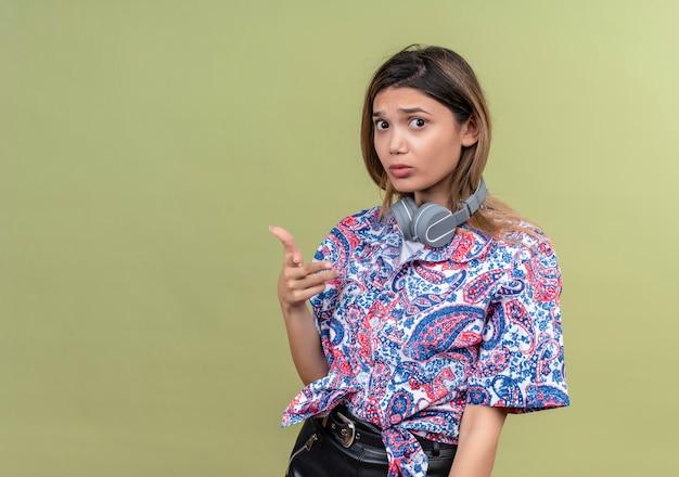 Una giovane donna confusa in camicia stampata paisley che indossa le cuffie sorridendo