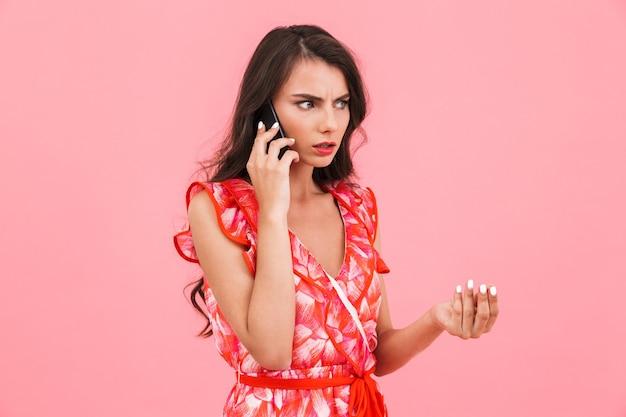 携帯電話で話している孤立した壁をポーズする混乱した若い女性。