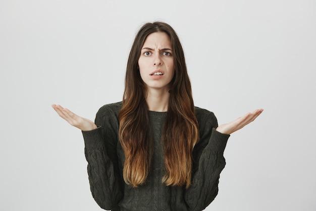 Смущенная молодая женщина пожимает плечами и недоуменно смотрит в камеру