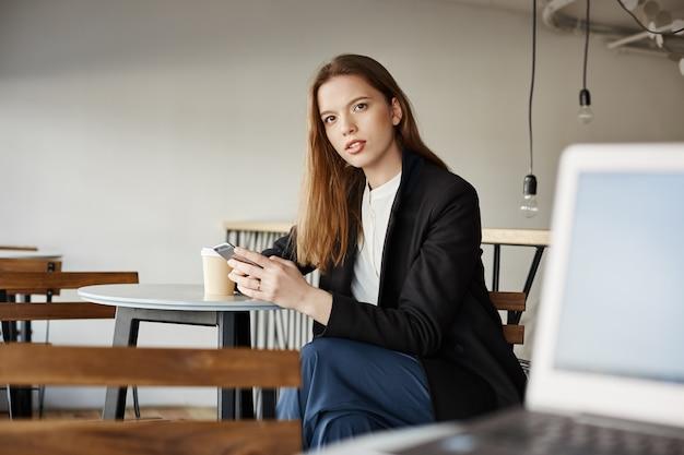 Giovane donna confusa che si siede nella caffetteria con smartphone e guardando interrogato qualcuno