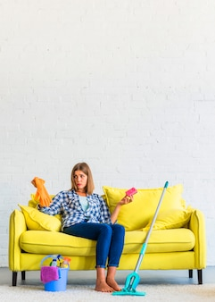 Confused young woman sitting on yellow sofa holding gloves and brush