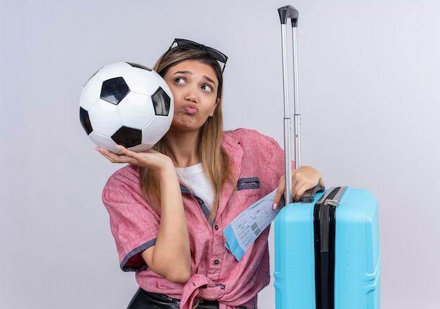 A confused young woman wearing red shirt and sunglasses looking up camera while holding ball with plane tickets and blue suitcase on a white wall