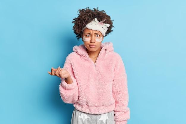 巻き毛の混乱した若い女性はsleepmaskを着用し、手のひらを上げるのをためらって目の下にコラーゲンパッチを適用し、青い壁に孤立したしわを減らします