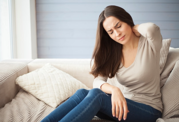Confused young woman with severe back pain and headache sitting on the couch at home