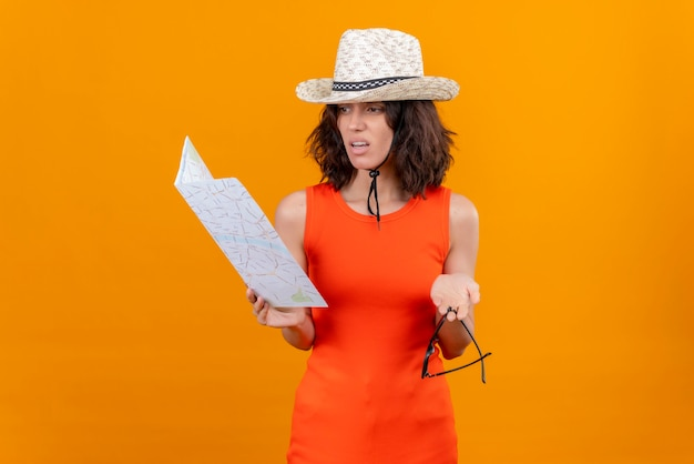 Una giovane donna confusa con i capelli corti in una camicia arancione che porta gli occhiali da sole della tenuta del cappello del sole che esamina la mappa