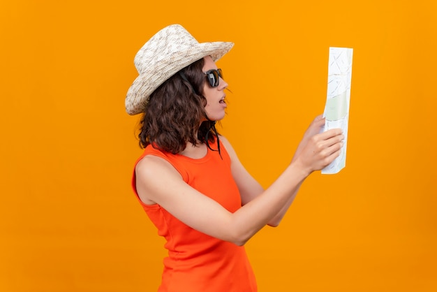 A confused young woman with short hair in an orange shirt wearing sun hat and sunglasses raising map with hands and looking attentively at it