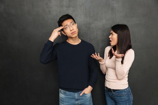 Confused азиатский человек показывая жест оружия пока слушающ его подруга