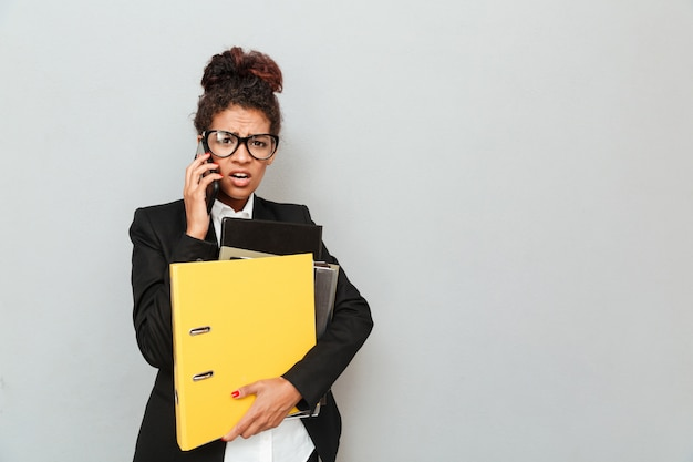 Confused молодая африканская бизнес-леди держа папки.