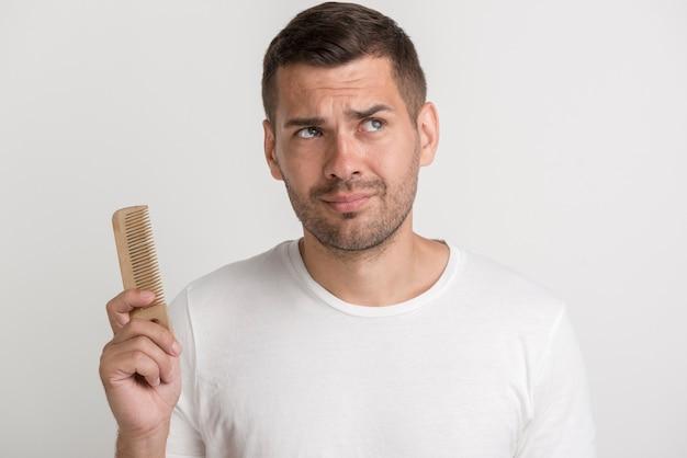 Confused молодой человек держа гребень смотря отсутствующий стоять против белой стены