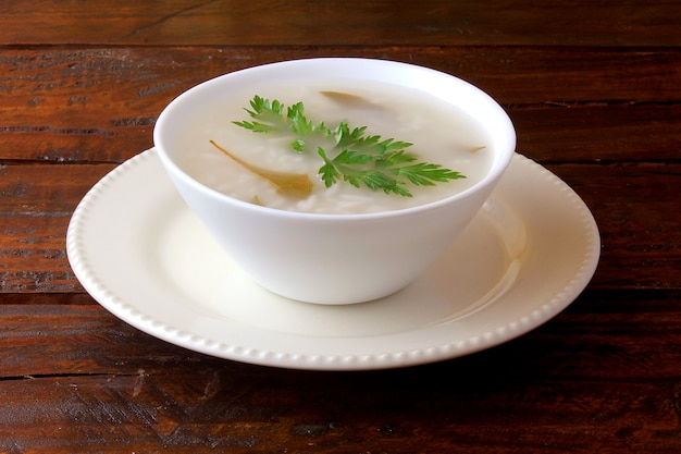 Congee in ceramic bowl on rustic wooden table, traditional rice porridge typical of asian cuisine