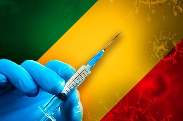 콩고 코비드19 예방 접종 캠페인 파란색 고무 장갑을 끼고 깃발 앞에 주사기를 들고 있습니다