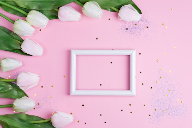 Congrats card with photo frame and corner border from white tulips flowers on a light pink background.