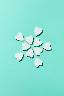 Поздравление с праздничным цветущим узором из маленьких гипсовых сердечек ручной работы на пастельной бирюзовой стене с жесткими тенями, копией пространства. вид сверху.