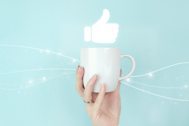 Congratulate, good and like concept. cropped view of female hand with white coffee cup and hand tumb up on blue background. tumb up concept.