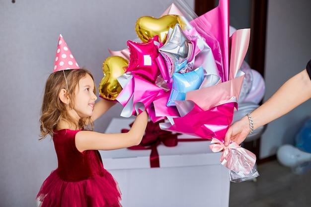 Поздравляет именинницу и дарит ей разноцветный букет шариков.