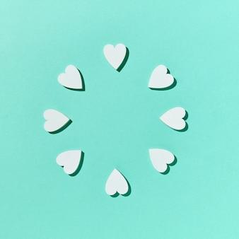 Поздравительная праздничная круглая рамка из гипсовых сердечек ручной работы на пастельно-бирюзовой стене с жесткими тенями, копией пространства. плоская планировка. валентина