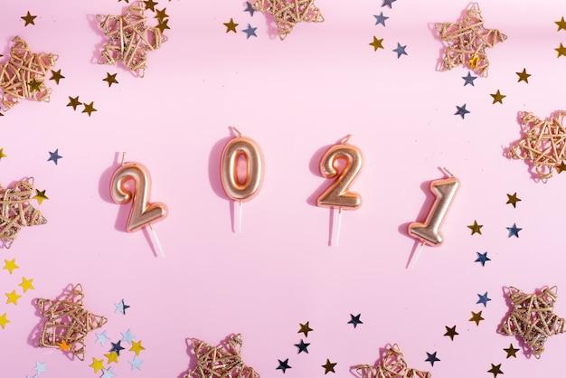 数字2021、明るい紙吹雪と淡いピンクの星の装飾が施されたおめでとう年賀状。フラットレイ。