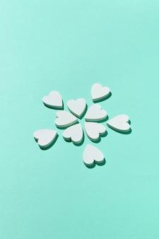 Поздравительная открытка-валентинка с креативным цветочным узором из маленьких гипсовых сердечек на светло-бирюзовой стене с жесткими тенями, копией пространства. поздравительная открытка.