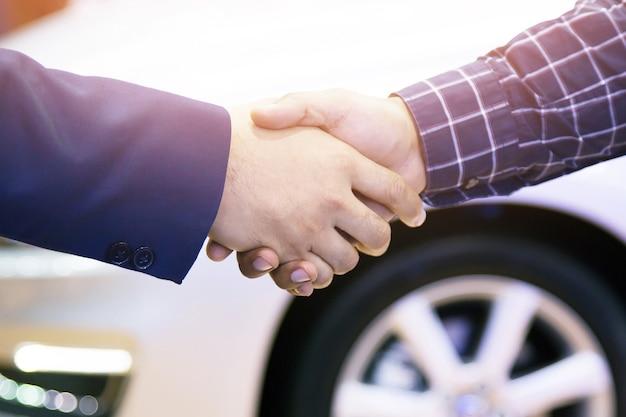 おめでとう。取引が成功した後、自動車ショーで自動車ディーラーと握手を交わす青年実業家の接写。