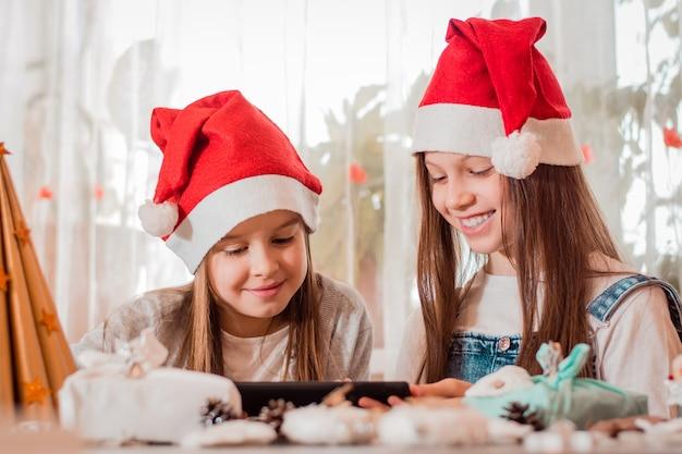 검역을 축하합니다. 크리스마스 장식을 한 소녀들은 태블릿을 통해 웃고 가족과 소통합니다.
