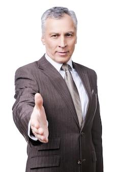 Поздравляю! портрет жизнерадостного зрелого мужчины в строгой одежде, протягивающего руку для тряски, стоя на белом фоне