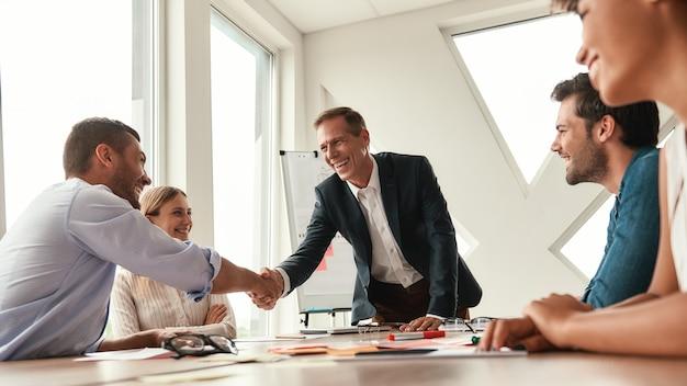 おめでとうございます2人の陽気な同僚が、現代のオフィスに座って握手し、笑顔を見せています。チームワーク。ミーティング