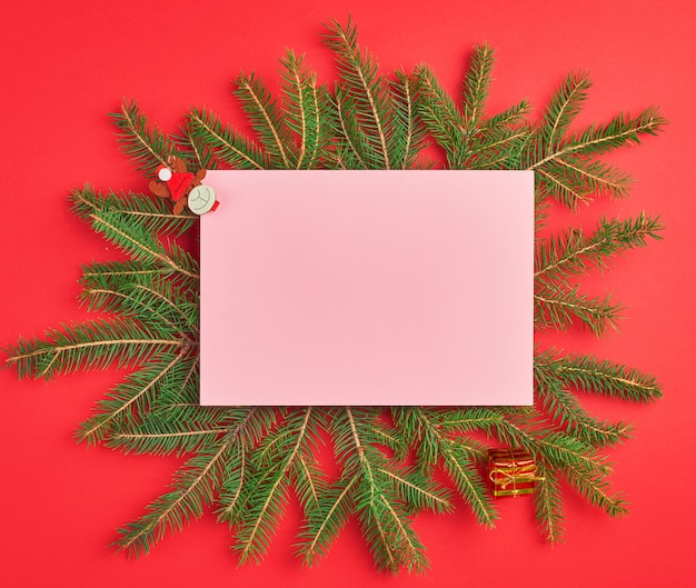 Congratulatory christmas background with an empty pink sheet and green branches
