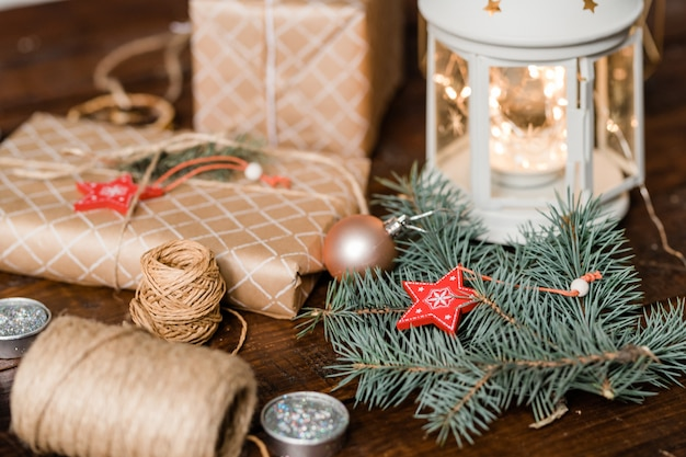 Conifer with chrismas star decoration, wrapped giftboxes, threads, candles and lantern making holiday composition