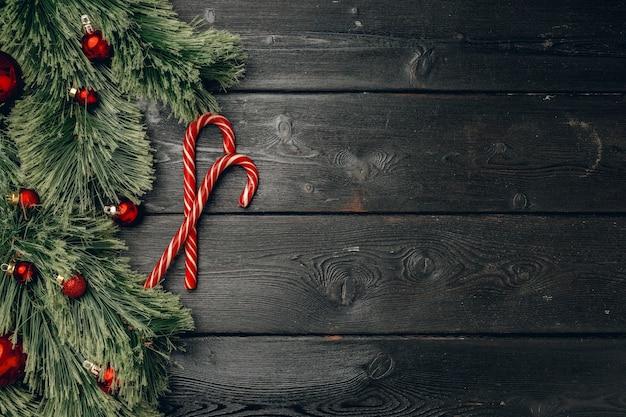 針葉樹の枝と黒い木の板のキャンディケイン