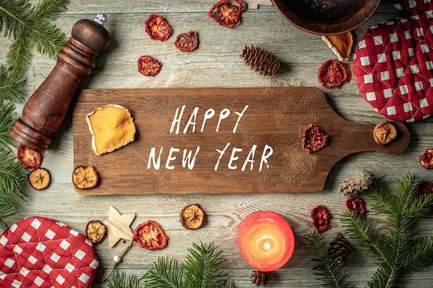 針葉樹の枝、お祭りやキッチンのアクセサリー、木製の背景に新年あけましておめでとうございますの碑文と茶色のまな板。上面図