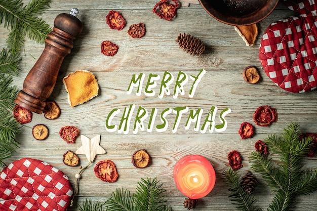 針葉樹の枝、メリークリスマスの碑文と木製の背景を持つお祝いとキッチンのアクセサリー。上面図。