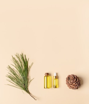 Coniferous spa aromatic essential cedar oil in small glass bottles, branch, cone on beige backdrop. aromatherapy and spa concept. view from above, copy space. vertical orientation.