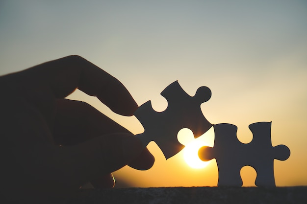 Connect jigsaw puzzle piece with sunset background.