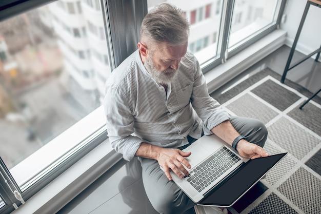 接続されています。床に座ってラップトップで作業している男性